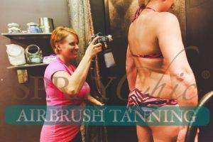 Carissa Serylo, SprayChic Airbrush Tanning Owner, applying custom airbrush tan